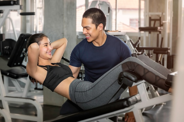 Young asian woman in sportswear training sit up with male trainer at fitness gym.