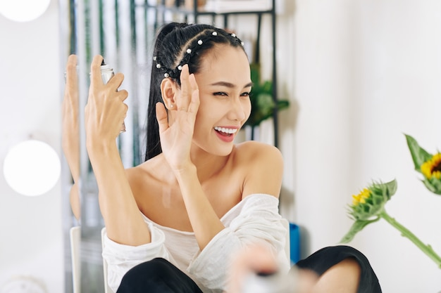 헤어 스프레이를 적용 할 때 눈을 가늘게 뜨고 손으로 얼굴을 덮는 젊은 아시아 여성