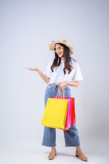 Young asian woman stand holding a multicolored shopping bag and stretched out her hand with a happy face on white background.