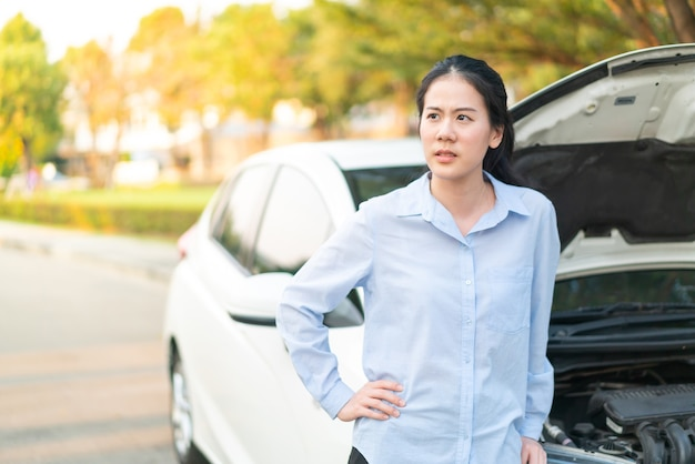 Young asian woman standing near broken down car with popped up hood having trouble with her vehicle