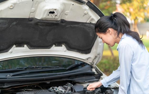 壊れた車の近くに立っている若いアジア人女性が彼女の車に問題を抱えているポップアップフード