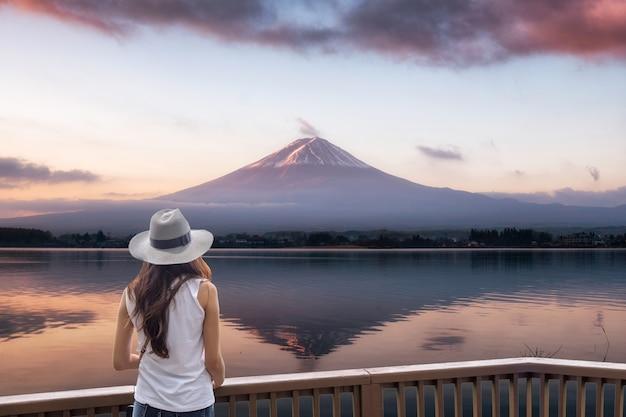 Молодая азиатская женщина, стоящая на деревянном балконе, глядя на гору фудзи сан