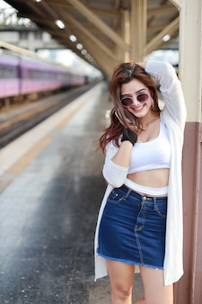 Young asian woman standing in train station with smiling and beauty face