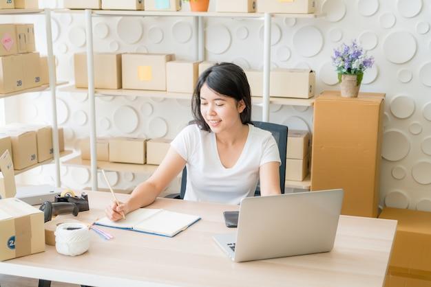 Молодая азиатская женщина запускает владельца малого бизнеса работая с цифровой таблеткой на рабочем месте.