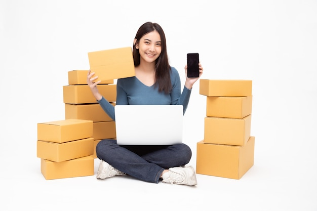 Young asian woman startup small business freelance holding parcel box, mobile phone and computer laptop and sitting on floor isolated, online marketing packing box delivery concept