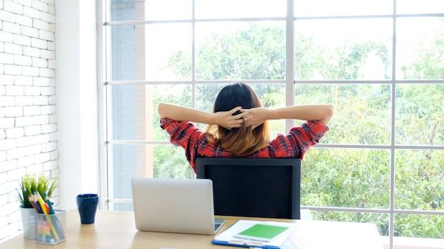 彼女の机のホームオフィスでラップトップコンピューターでの作業中に体を伸ばして若いアジア女性