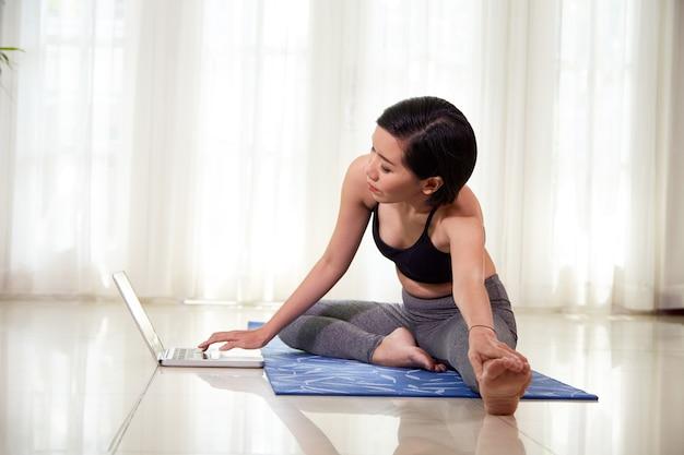 ノートパソコンの画面でチュートリアルに従うときに足を伸ばす若いアジアの女性