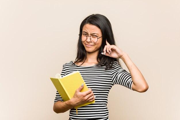 手で耳を覆う本を持っている若いアジアの女性学生。