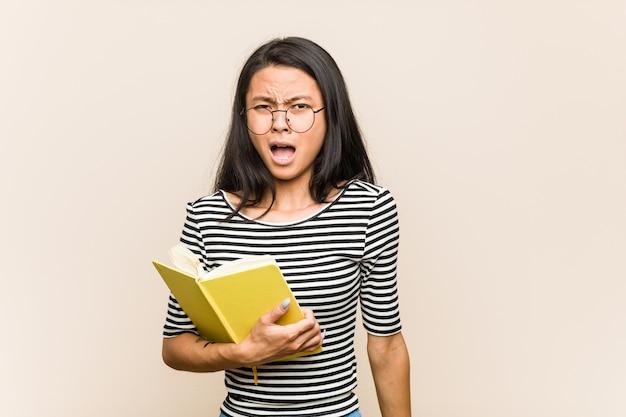 非常に怒っていると積極的に叫んで本を持っている若いアジア女性学生。