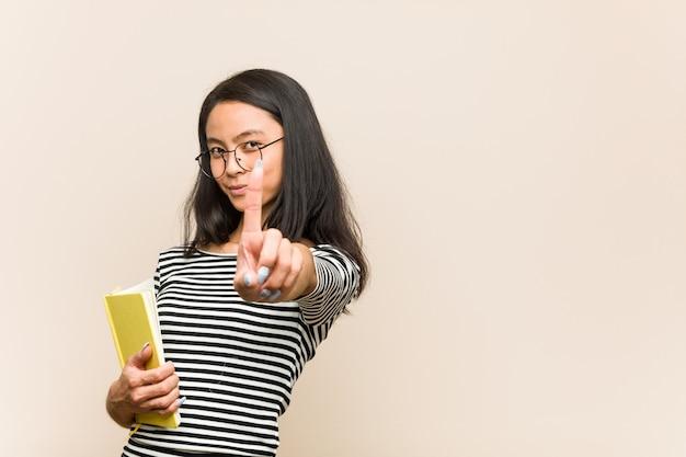 指でナンバーワンを示す本を保持している若いアジア女性学生。