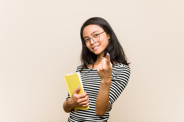 Young asian woman student holding a book pointing with finger at you as if inviting come closer.