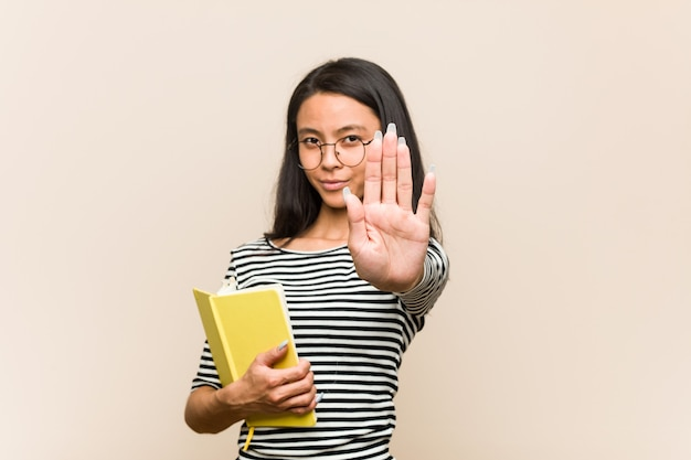 Young asian woman student holding a book standing with outstretched hand showing stop sign, preventing you.