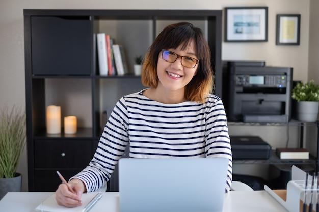 若いアジアの女性の研究とコンピューターとノートブックに取り組んでいます。幸せな笑顔。