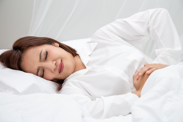 Young asian woman suffering from abdominal pain or stomach ache while sleeping on white bed at home