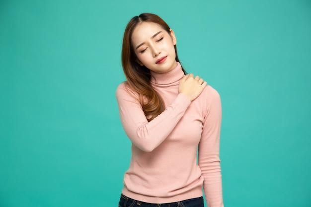 Молодая азиатская женщина страдая от боли в плече изолированном на зеленой предпосылке.