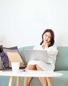 ノートパソコンを使用すると肩の痛みに苦しんでいる若いアジアの女性