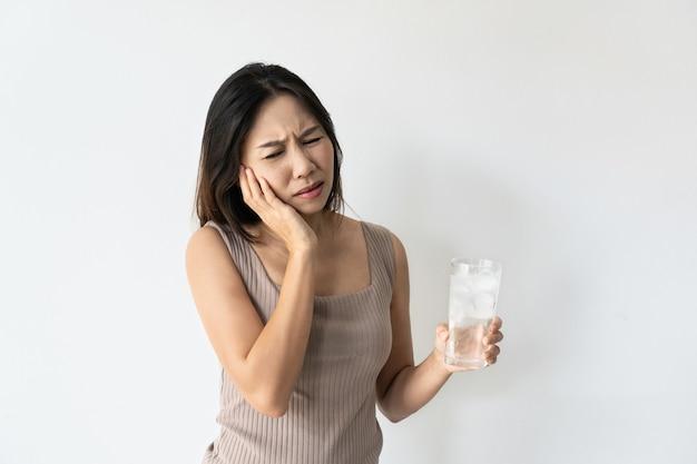 歯痛と氷と冷たい水のガラスを持っている手に苦しんでいる若いアジアの女性。冷たい飲み物を飲む女の子、角氷でいっぱいのガラスと歯の痛みを感じるヘルスケアの概念。
