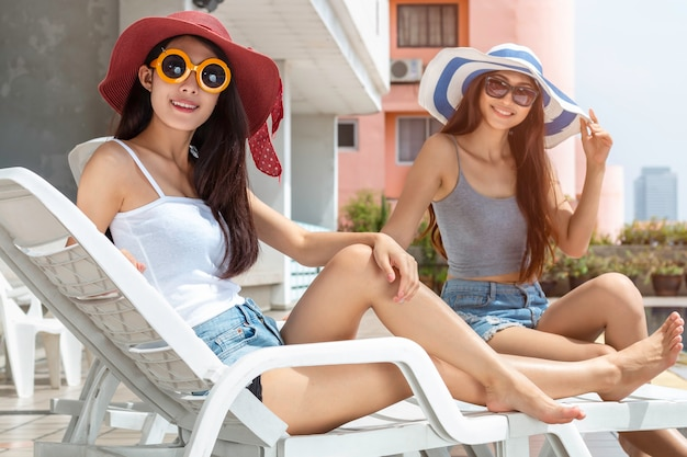 Young asian woman in sunglasses relaxing and sitting on beach chair.
