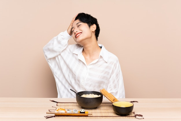 Young asian woman in a table with bowl of noodles and sushi laughing