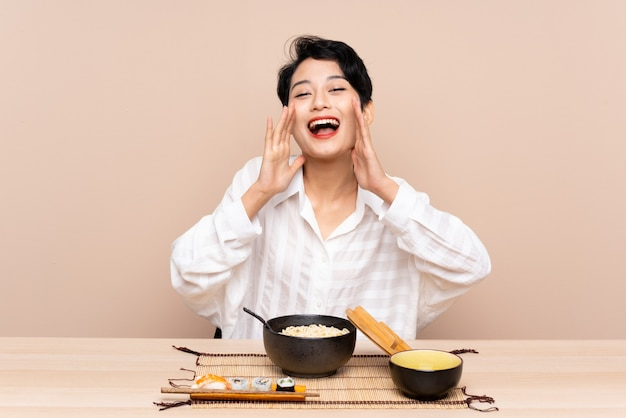 Young asian woman in a table with bowl of noodles and sushi shouting with mouth wide open