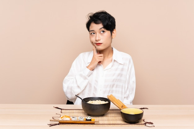 Young asian woman in a table with bowl of noodles and sushi thinking an idea