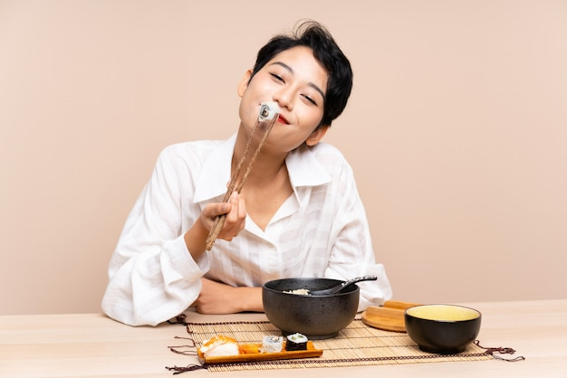 Young asian woman in a table with bowl of noodles and sushi