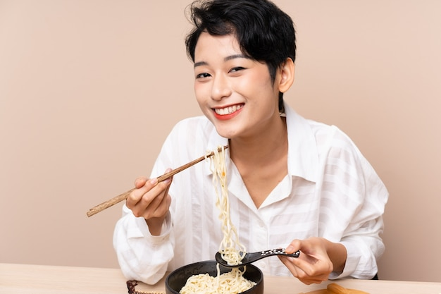 Young asian woman in a table with bowl of noodles