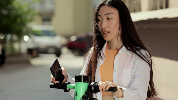 若いアジアの女性は、電動スクーターを借りるために電話アプリケーションを使用して駐車場観光電話アプリケーションの女性を共有する電動スクーターを取ります