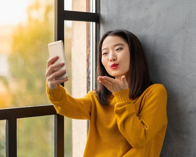 セルフィーを取り、キスを吹く若いアジアの女性。窓に座って彼氏とビデオ通話を介して通信している真っ赤な唇を持つ美しい10代の少女