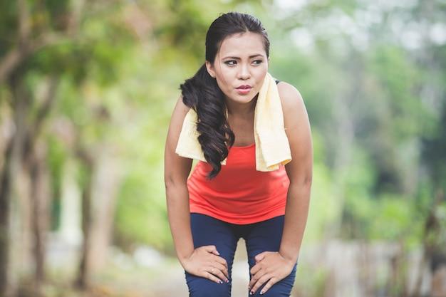 Молодая азиатская женщина принимая перерыв после бежать в парке