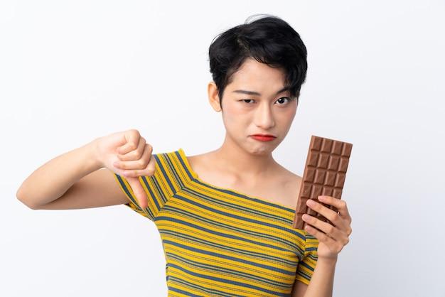 Молодая азиатская женщина принимая таблетку шоколада делая плохой сигнал