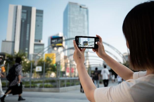 Молодая азиатская женщина, делающая фото со своим телефоном