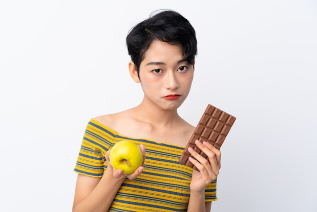 Young asian woman taking a chocolate tablet in one hand and an apple in the other