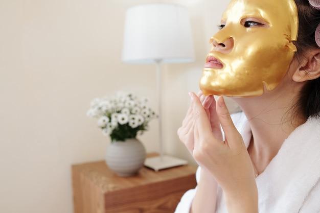 若返りと保湿の黄金のシートマスクを脱いで若いアジアの女性
