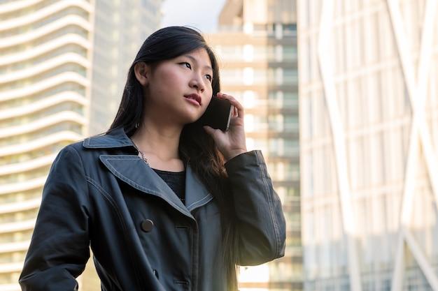 市内で電話で話している若いアジアの女性