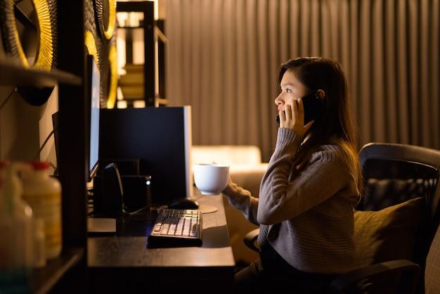 自宅で夜遅くまで仕事をしながら電話で話している若いアジア女性