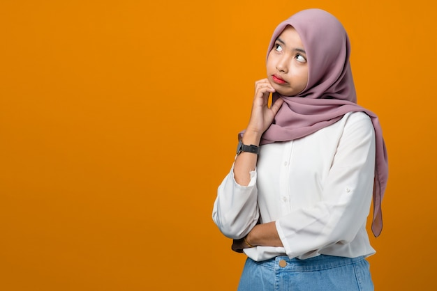Молодая азиатская женщина думает и чувствует себя смущенной на желтом