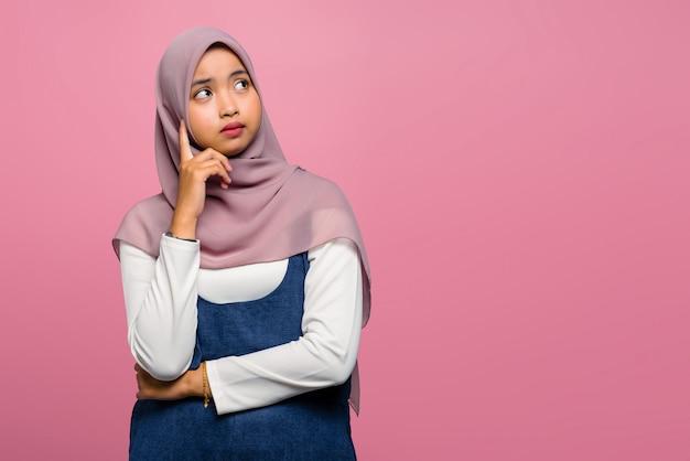 생각 하 고 hijab를 착용하는 젊은 아시아 여자