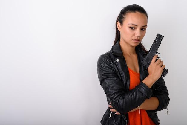 Молодая азиатская женщина думает, глядя вниз и держа пистолет против белого пространства