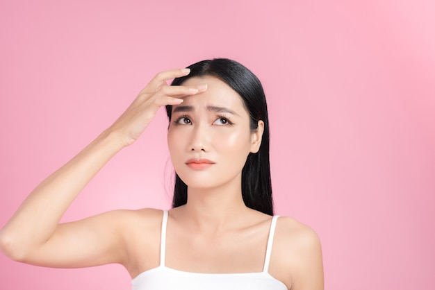 Young asian woman touch and worry about her fac