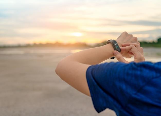 Молодая азиатская женщина касаясь умному диапазону после бежать в утре. носимый компьютер. браслет для пульсометра. фитнес-устройство. активный или фитнес-трекер.