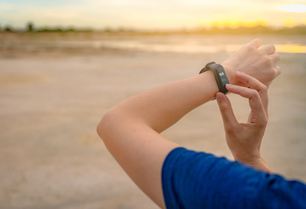 Молодая азиатская женщина касаясь умному диапазону после бежать в утре. носимый компьютер. браслет для пульсометра. фитнес-устройство. смарт-часы подключили устройство. браслет