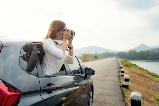 Young asian woman tourist taking photo in car with camera driving on road trip travel vacation. girl passenger taking picture out of window with beautiful view lake and mountains