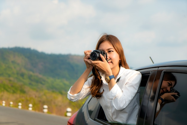 Young asian woman tourist taking photo in car with camera driving on road trip travel vacation.