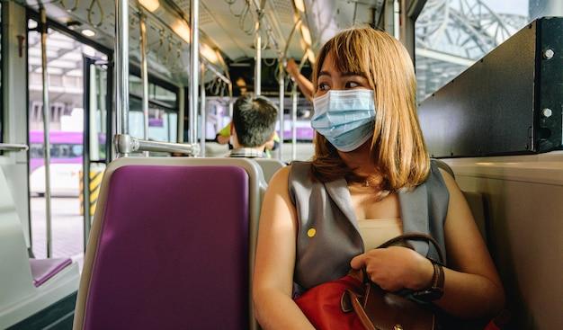 Covid-19ウイルスの発生時に空港でフェイスマスクを身に着けている若いアジアの女性観光客。