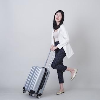 旅行する荷物を持つ若いアジア女性観光客