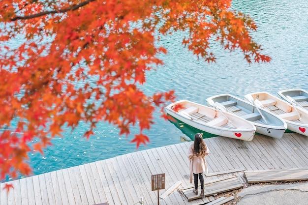 Молодая азиатская женщина-путешественница, наслаждающаяся видом на красный кленовый лист на госикинуме или пятицветном пруду осенью в префектуре фукусима, япония