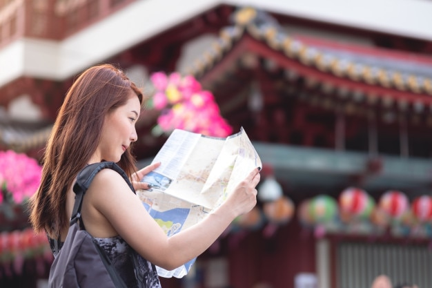 Young asian woman traveler holding map in chinatown, singapore