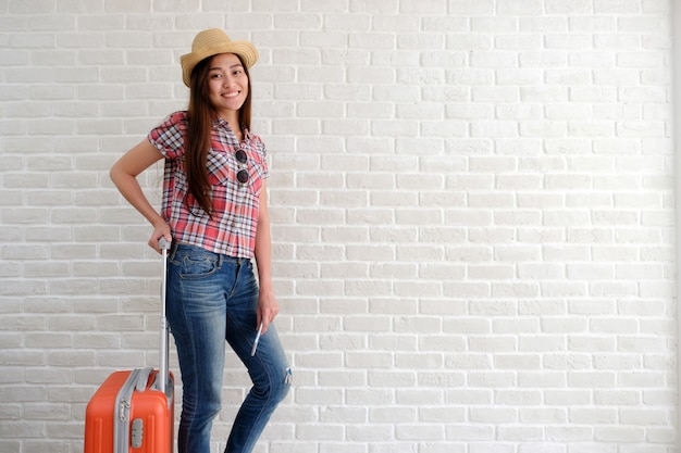 Young asian woman traveler holding smart phone and  luggage in white room .