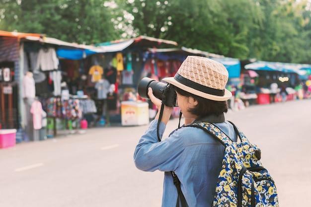 Молодая женщина-путешественница, фотографирующая на уличном рынке